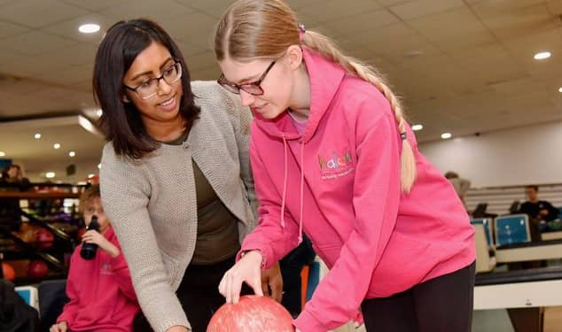 woman helping child with bowling ball